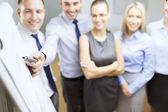 Equipe de negócios sorridente com gráficos na placa de aleta — Fotografia Stock