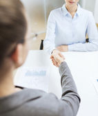 Two calm businesswoman shaking hands in office — Stock Photo