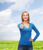 Smiling girl in casual clothes showing thumbs up — Stock Photo