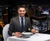 Smiling man with tablet pc eating main course — Stock Photo