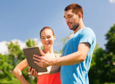 Smiling couple with tablet pc outdoors — Stock Photo