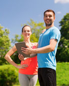 Smiling couple with tablet pc outdoors — Photo