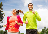 Smiling couple with earphones running outdoors — 图库照片