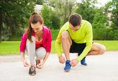 Smiling couple tying shoelaces outdoors — Stock Photo