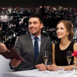 Waiter giving menu to happy couple at restaurant — Stock Photo #50288681