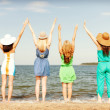 Girls with hands up on the beach — Stock Photo