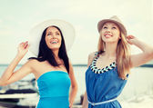Girls in dresses with hats on the beach — Stock Photo