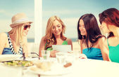 Smiling girls looking at tablet pc in cafe — Stock Photo