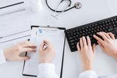 Doctor and nurse writing prescription paper — Stock Photo