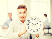 Businesswoman showing white clock in office — Stock Photo