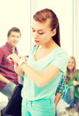 Student girl looking at wristwatch — Stock Photo