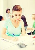 Jeune fille étudiante avec carnet et les calculatrice — Photo