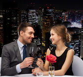 Young couple with glasses of wine at restaurant — Stock Photo