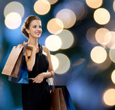 Smiling woman in dress with shopping bags — Stock Photo
