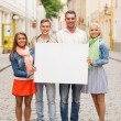 Group of smiling friends with blank white board — Stock Photo #50370831