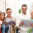 Group of friends with city guide, map and camera — Stock Photo #50371551