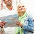 Happy couple with map exploring city — Stock Photo