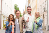 Group of smiling friends showing thumbs up — Stock Photo