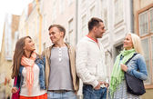 Group of smiling friends walking in the city — Stock Photo