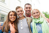 Group of smiling friends in city — Stock Photo