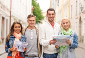 Group of smiling friends with city guide and map — Stockfoto