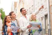 группа улыбающихся друзей с руководства города и карте — Стоковое фото