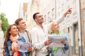 Grupa uśmiechniętych przyjaciół z przewodnika i mapy miasta — Zdjęcie stockowe