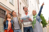 Group of smiling friends with map exploring city — Stock Photo