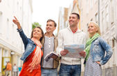 Group of smiling friends with city guide and map — Foto de Stock