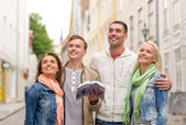 Group of friends with city guide exploring town — Stok fotoğraf