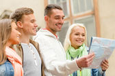 Group of friends with map exploring city — Stock Photo