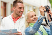Smiling couple with map and photocamera in city — Stock Photo