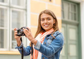 Smiling girl with digiral photocamera in the city — Stock Photo