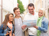 Group of smiling friends with map and photocamera — Stock Photo