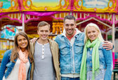 Group of smiling friends in amusement park — Stock Photo