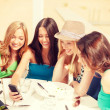 Girls looking at smartphone in cafe on the beach — Stock Photo #50423557