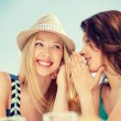 Girls gossiping in cafe on the beach — Stock Photo #50423727