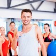 Smiling man standing in front of the group in gym — Stock Photo #50424153