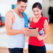 Two smiling people with tablet pc in the gym — Stock Photo