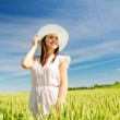 Smiling young woman in straw hat on cereal field — Foto Stock