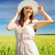 Smiling young woman in straw hat on cereal field — Stock Photo #50425867