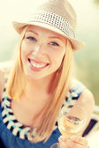 Smiling girl in hat with champagne glass — Stockfoto