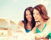 Chicas mirando smartphone en café en la playa — Foto de Stock