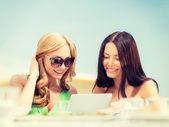 Cafe tablet pc bakarak gülümseyen kızlar — Stok fotoğraf
