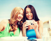 Girls with camera in cafe on the beach — Stock Photo