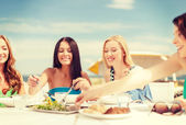 Smiling girls in cafe on the beach — Stockfoto