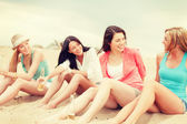 Smiling girls with drinks on the beach — Stock Photo
