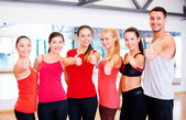 Groupe de personnes dans la salle de gym montrant les pouces vers le haut — Photo