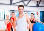Smiling man standing in front of the group in gym — Stock Photo