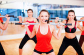 Group of smiling people working out with barbells — Stock Photo